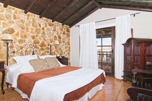 Dormitorio con pared de piedra natural y vigas de madera